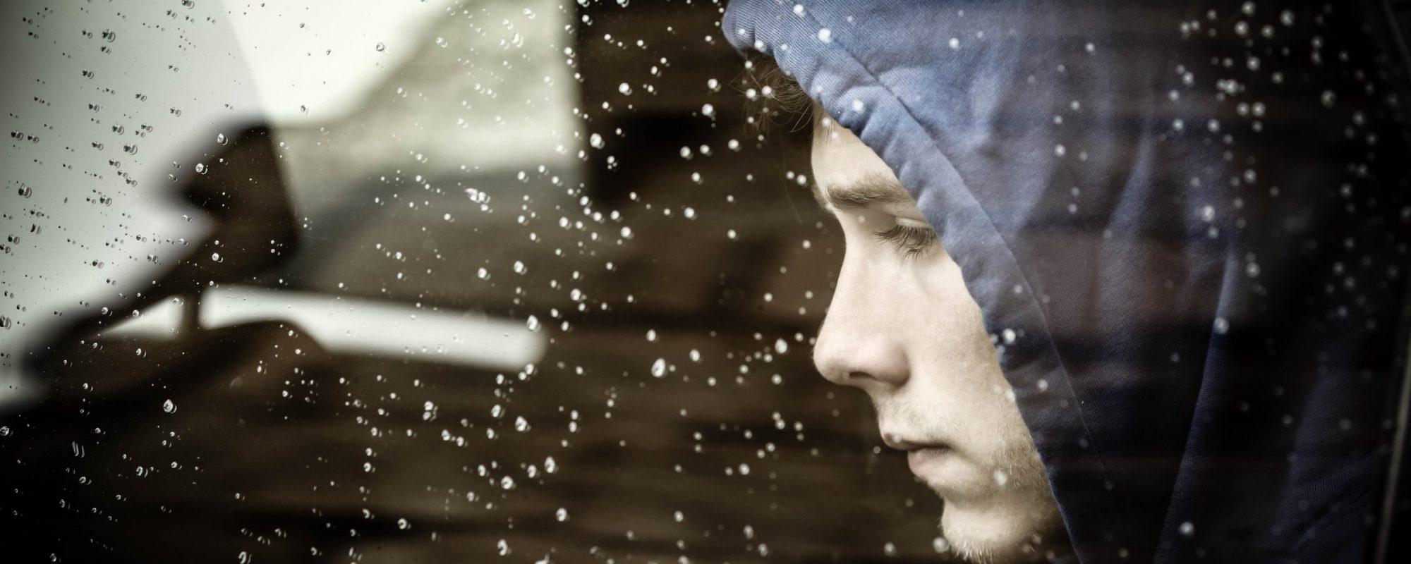 Sad teenager boy worried inside a car